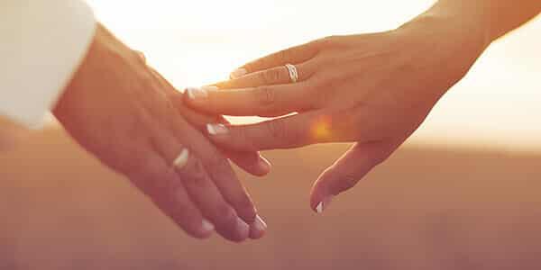 Hände mit Eheringen berühren sich