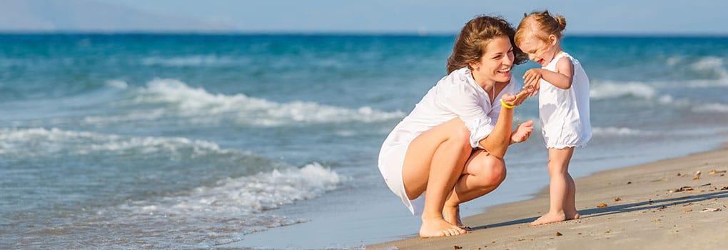 Geschiedene Mutter mit Kind im Urlaub am Strand
